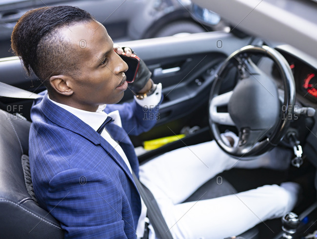 From below serious ethnic male entrepreneur in classy suit with bow tie driving luxury car while talking on smartphone and looking away