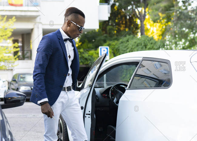 Side view of serious African American male entrepreneur closing door of luxury automobile parked on road in city