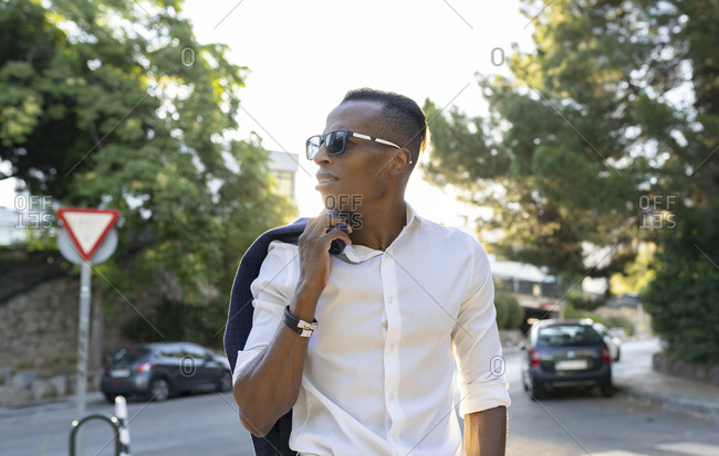 Stylish African American businessman with jacket on shoulder and in sunglasses walking along street in city and looking away