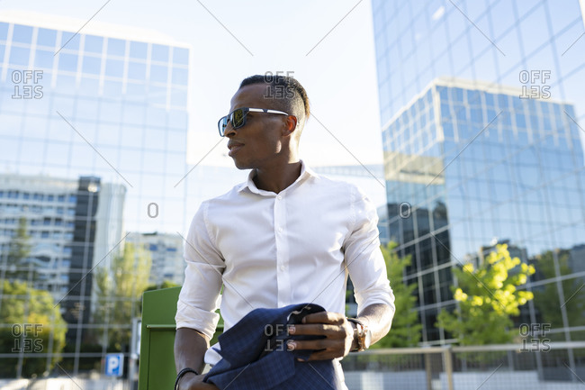 From below stylish African American businessman with jacket on shoulder and in sunglasses walking along street in city and looking away