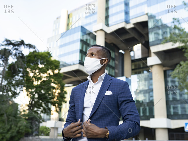 Serious black male entrepreneur in formal suit and medical mask standing in downtown waiting for meeting looking away