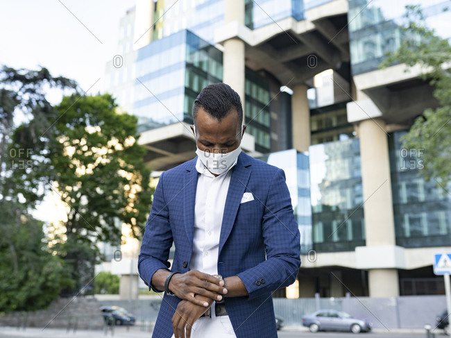 Low angle of serious black male entrepreneur in formal suit and medical mask standing in downtown and checking time on wristwatch while waiting for meeting