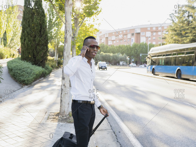 Stylish African American male entrepreneur standing with suitcase on roadside talking on the mobile phone while looking away