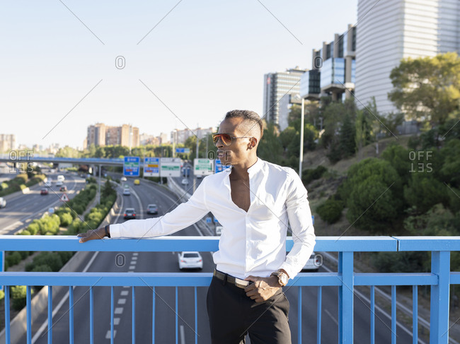 Determined African American male entrepreneur in white shirt standing near metal railing on bridge and looking away