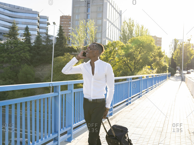 Cheerful ethnic male entrepreneur in classy wear walking with luggage along bridge and speaking on smartphone while looking away