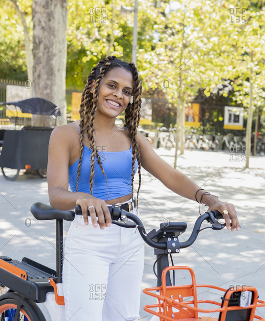 Young black cheerful woman posing with bike looking at camera on a sunny summer day looking at camera