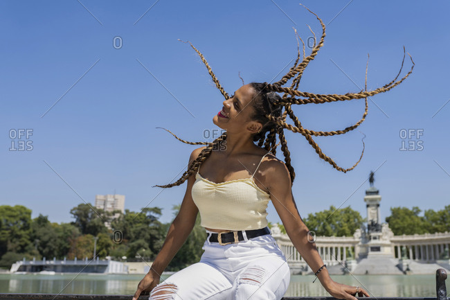 Carefree Hispanic female in trendy outfit and with braids sitting with flying hair on fence near lake in urban park and enjoying summer