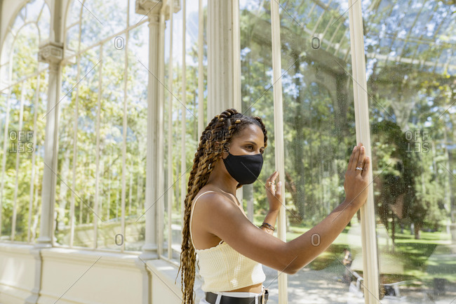 Trendy ethnic female with braids wearing protective mask standing in glass building lit by sunlight while looking through window
