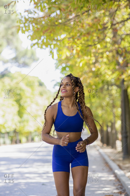 Slim Hispanic female in sportswear running along path in urban park while doing cardio training and looking away