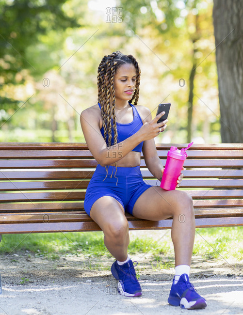 Side view of smiling Hispanic female athlete sitting on bench with bottle of water and browsing mobile phone while relaxing after workout in park