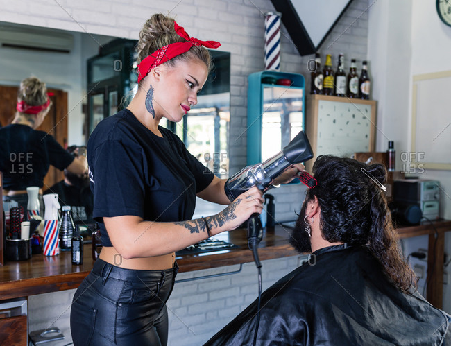Side view of stylish female master in black leather pants drying hair of bearded male client while working in barbershop