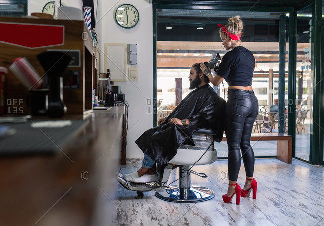 Side view of stylish female master in black leather pants and red high heels drying hair of bearded male client while working in barbershop
