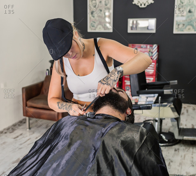 High angle of crop unrecognizable tattooed barber with scissors and comb cutting beard of stylish man sitting in chair in modern salon