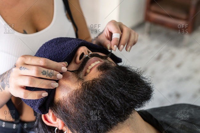 High angle of crop unrecognizable female master with tattooed body styling mustache of happy brutal bearded man with piercing during haircut procedure in barbershop