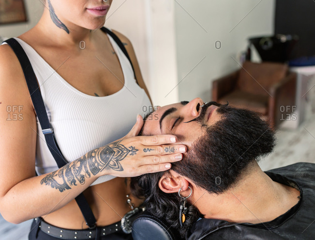 Side view of crop anonymous tattooed barber doing massage on beard of relaxed male client during grooming procedure in barbershop
