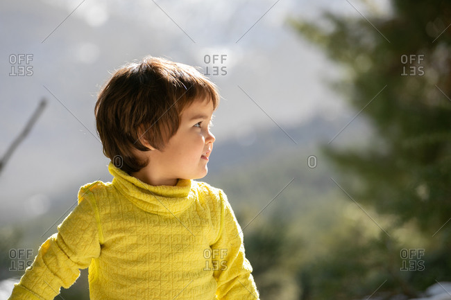 Cute kid in warm clothes walking on hill in highlands in winter while looking away