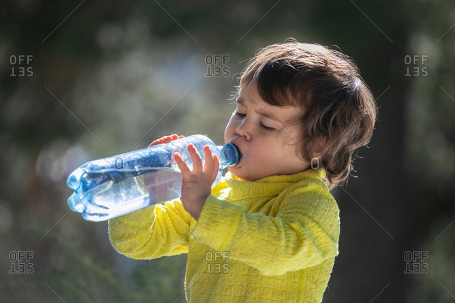 Serious kid standing in nature on sunny day and drinking fresh clean water from plastic bottle