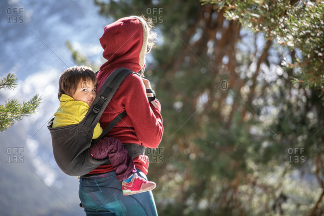 Side view of woman with kid in baby carrier behind back standing on hill in highlands on sunny day in winter