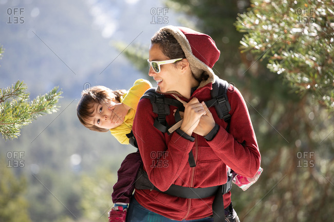 Woman with kid in baby carrier behind back standing on hill in highlands on sunny day in winter