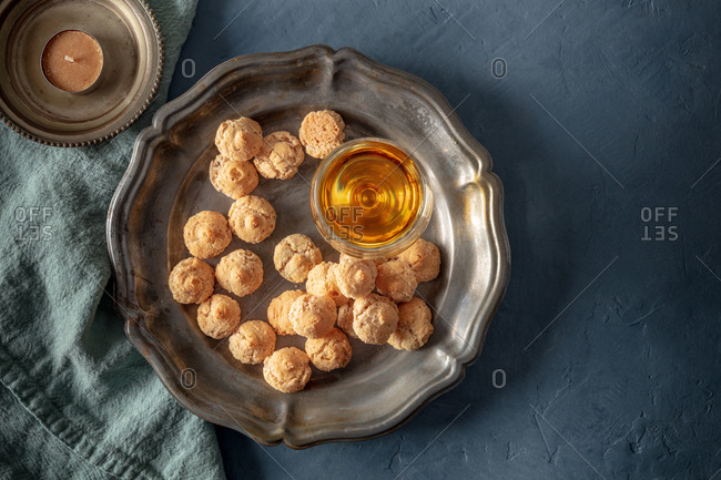 Top view of Amaretti, Italian cookies, with a glass of Amaretto, overhead shot with a place for text on a dark blue background