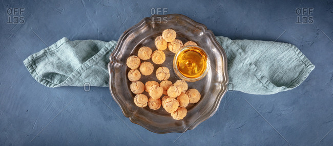 Top view of Amaretti, traditional Italian almond cookies, with Amaretto liqueur, overhead panorama with copy space, on a dark blue background
