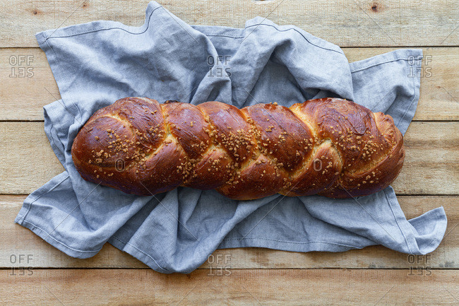 Top view of appetizing aromatic braided bread with seeds placed on linen napkin on wooden table