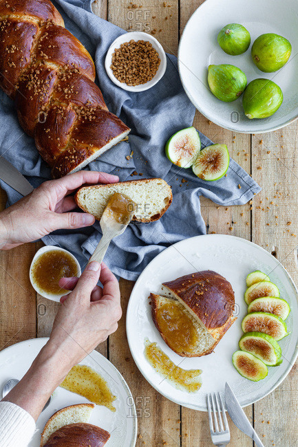Top view of crop unrecognizable female spreading sweet fig jam on piece of fresh braided bread served with fresh fruits on wooden table