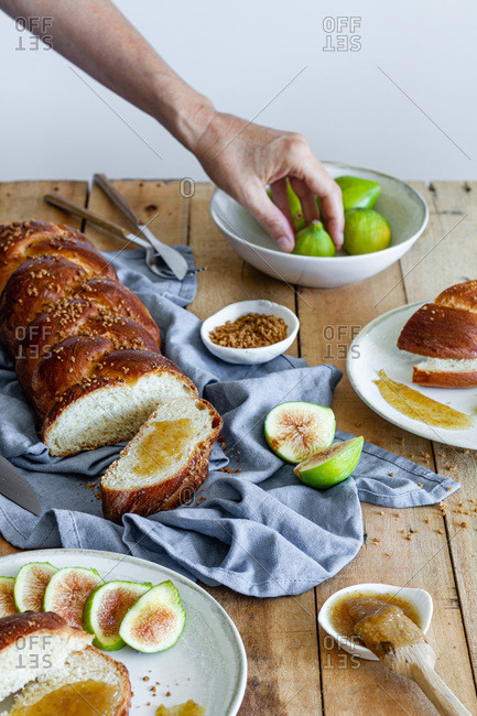 Crop unrecognizable female holding fresh fig fruit near piece of fresh braided bread with sweet fig jam on wooden table