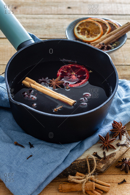 High angle of saucepan with hot tasty mulled wine with cinnamon stick and dried oranges arranged on table with star anise and dry cloves in kitchen