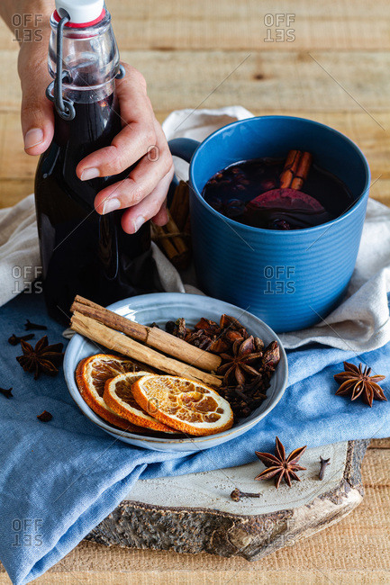 High angle of unrecognizable crop male with glass bottle of homemade mulled wine arranged on table with aromatic cinnamon sticks and dried oranges