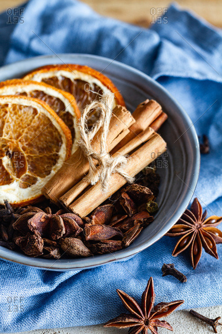 High angle of bowl with aromatic cinnamon sticks and dried oranges arranged on table with star anise and cloves