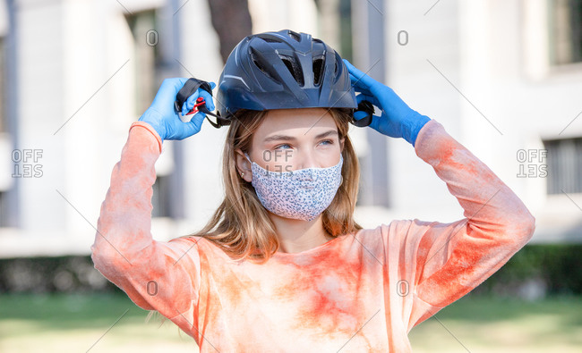 Young female cyclist in protective mask and gloves putting on hardhat and looking away on street of Madrid, Spain