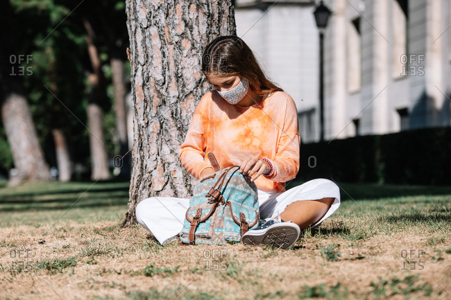 Young female student in mask sitting under tree outside university and rummaging through backpack on sunny day in Madrid, Spain