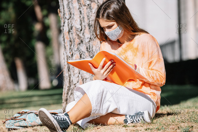Young woman in face mask sitting near tree trunk and reading notes in planner while doing homework on sunny day in Madrid, Spain