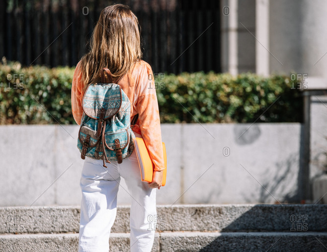 Back view of anonymous young female with backpack and notepad walking to studies on sunny day on street of Madrid, Spain