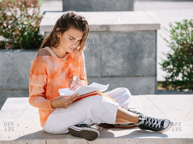 Low angle of young woman in casual clothes sitting cross legged on border and opening notepad while doing homework outside university building in Madrid, Spain