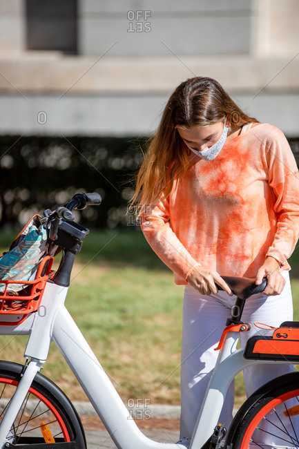Young girl prepares the bicycle seat to her height before renting