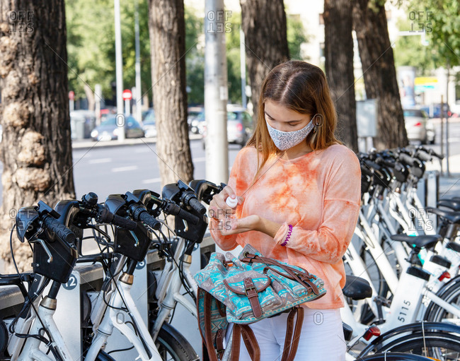female spraying sanitizer on hand on blurred background of bicycle parking lot in Madrid, Spain
