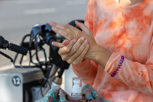Anonymous girl cleans her hands after applying hydroalcoholic gel next to a bicycle parking lot on a street in Madrid, Spain