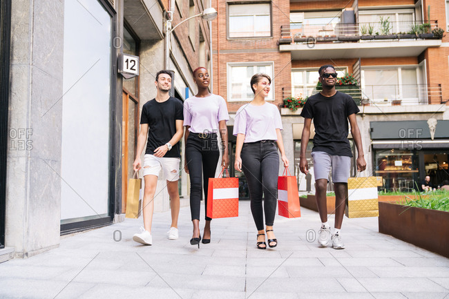 Low angle full length of group of cheerful multiracial millennial friends in trendy clothes carrying shopping bags and walking on urban street while enjoying shopping time together