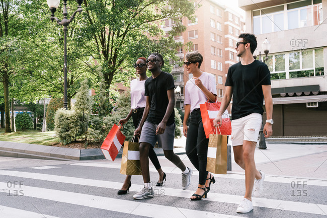 Full length of cheerful young diverse students in trendy outfits and sunglasses carrying purchases in shopping bags and chatting happily while crossing road on city street