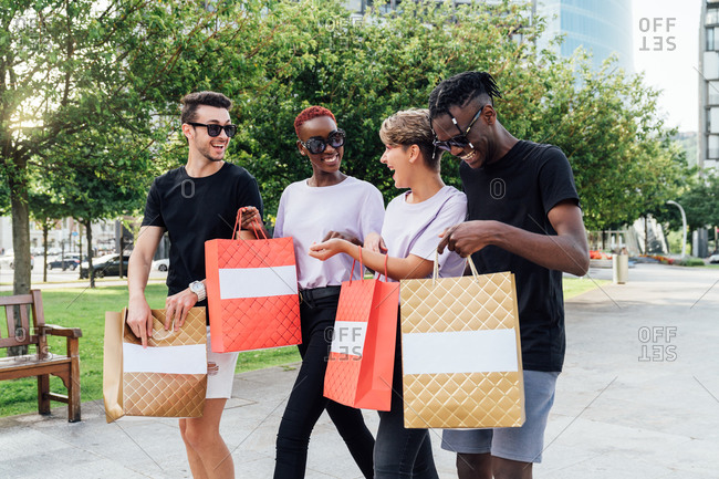 Cheerful young diverse students in trendy outfits and sunglasses carrying purchases in shopping bags and chatting happily while crossing road on city street