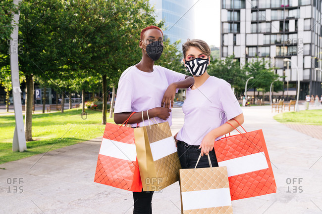 Stylish young multiethnic female friends in protective masks and similar wear  holding colorful shopping bags while standing on city street after shopping together during coronavirus pandemic