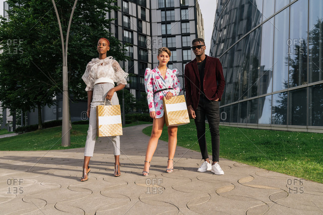 Full length of group of modern millennial multiethnic friends in fashionable outfits holding shopping bags while standing together against contemporary city buildings with glass walls