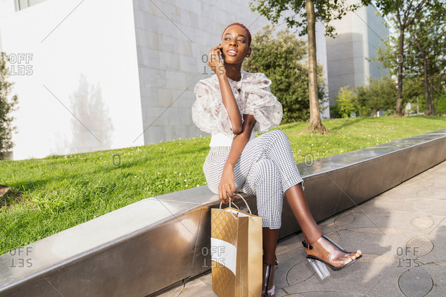 Young African American female with stylish haircut dressed in fashionable clothes and high heels with shopping bag in hand relaxing on stone border against modern urban building after shopping