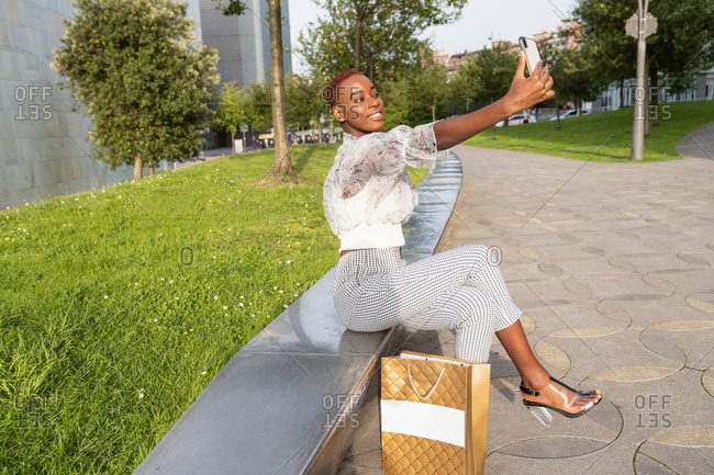 Young African American female with stylish haircut dressed in fashionable clothes and high heels with shopping bag taking a selfie relaxing with her mobile on stone border against modern urban building after shopping
