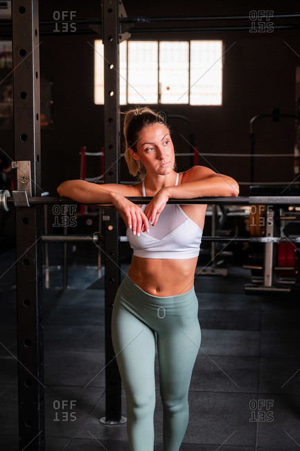 Confident muscular female in sports bra and leggings leaning on barbell while relaxing during workout in gym and looking away