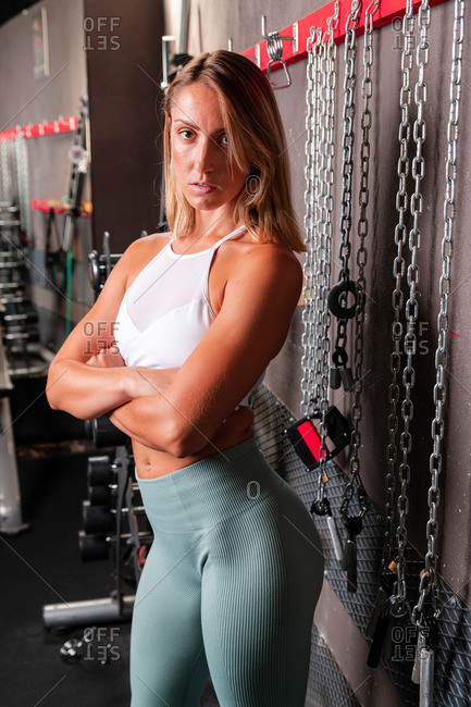 Portrait of confident muscular female in sports bra and leggings and with crossed arms looking at camera