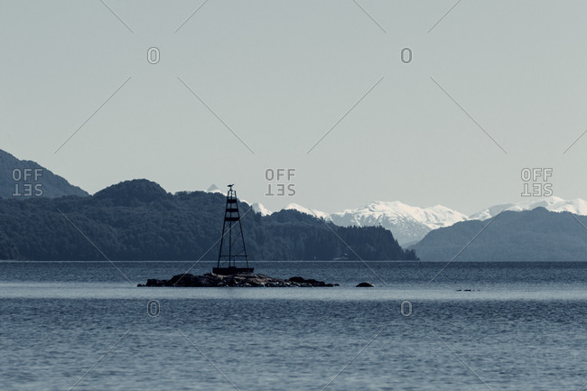 Picturesque view of metal tower on rock in sea on background of highlands covered with snow in Patagonia
