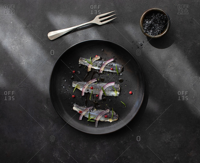 Top view of appetizing marinated sardines fish fillet with onion and herbs served on black plate with fork